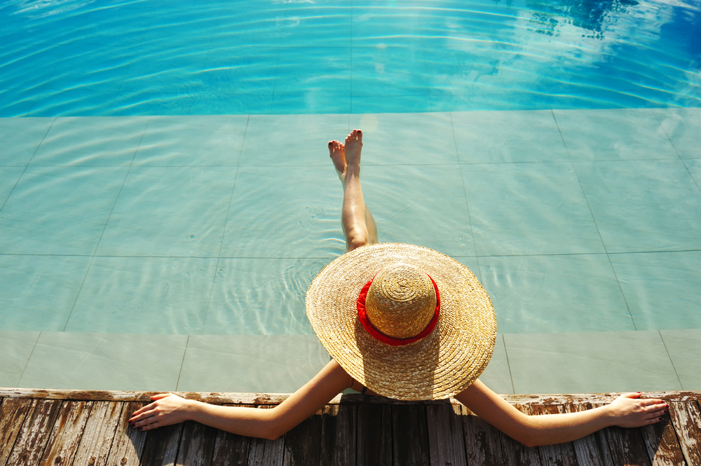 Travel - woman relaxing by pool