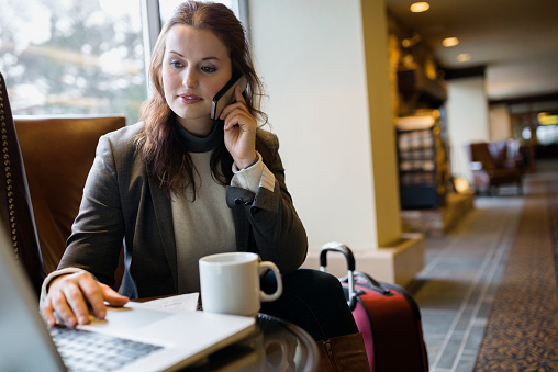 Businesswoman on cell phone working at laptop