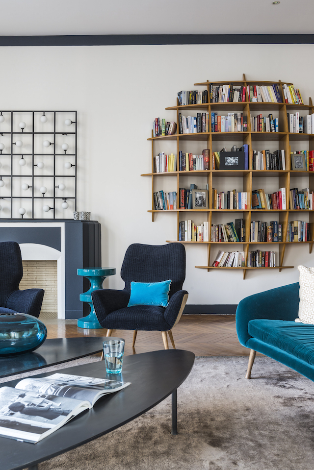 The 1950s oak round ?library? shelving unit was found at a Parisian fleamarket. The teal sofa is by Caravane, covered in Dedar fabric.