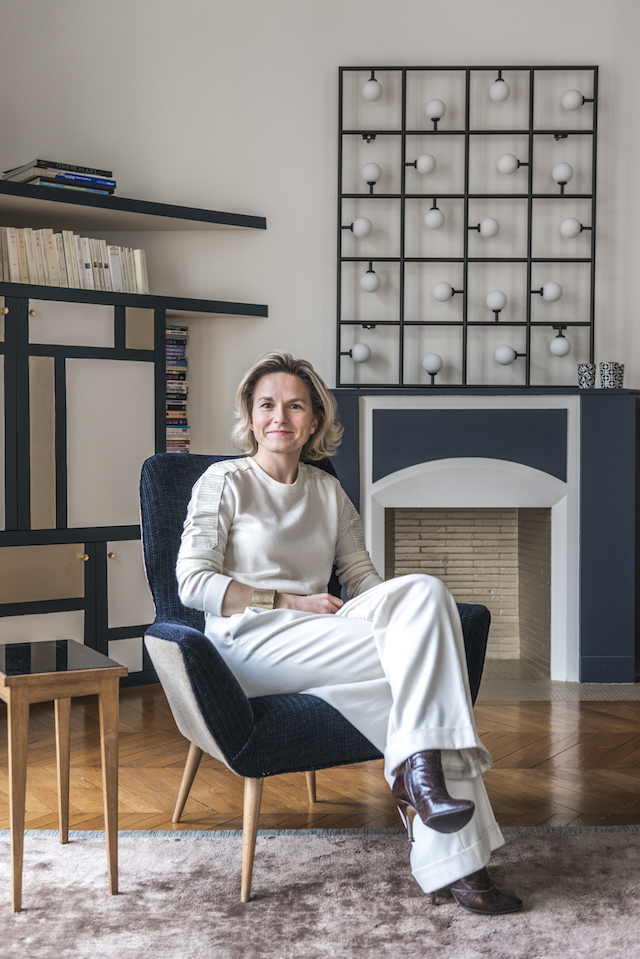 Interior designer Anne-Sophie proudly sits in the apartment she designed.