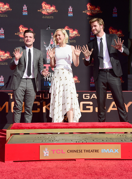 "HOLLYWOOD, CA - OCTOBER 31: (L-R) Actors Josh Hutcherson, Jennifer Lawrence and Liam Hemsworth attend Lionsgate's ""The Hunger Games: Mockingjay - Part 2"" Hand and Footprint Ceremony at TCL Chinese Theatre on October 31, 2015 in Hollywood, California. (Photo by Frazer Harrison/Getty Images)"