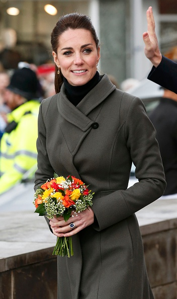 CAERNARFON, WALES - NOVEMBER 20: Catherine, Duchess of Cambridge carries a bunch of flowers from as she leaves after visiting a GISDA centre during a visit to Caernarfon on November 20, 2015 in Wales. (Photo by Phil Noble - WPA Pool/Getty Images)