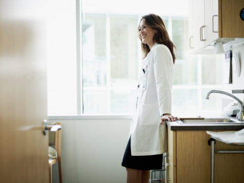 Female doctor leaning against counter in exam room smiling