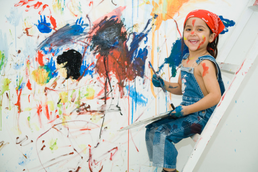 Portrait of girl (4-5) painting wall
