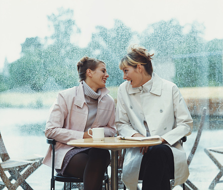 Two Women Talk at Cafe Table