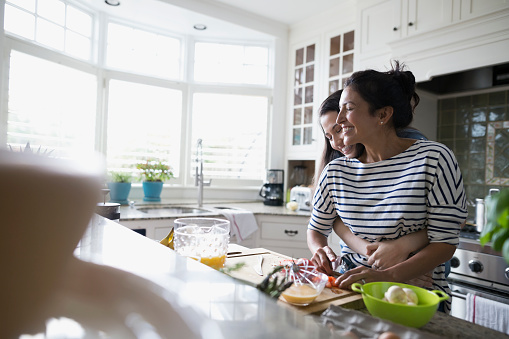 Mother and daughter hugging and cooking in kitchen