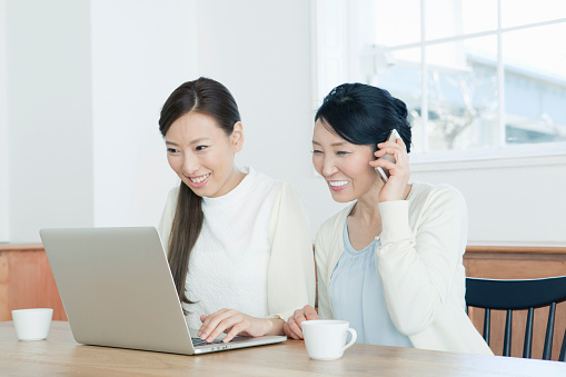 Mother using mobile phone next to daughter using laptop