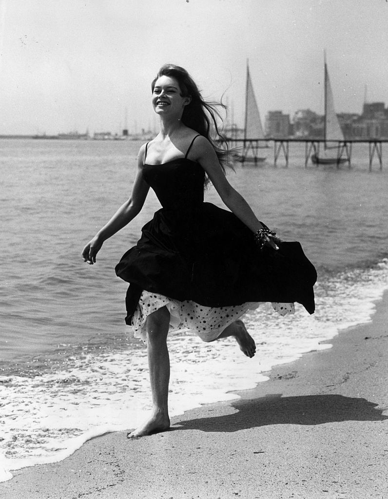 Running barefoot on the sands at Cannes, French film star, Brigitte Bardot (Camille Javal). (Photo by George W Hales/Getty Images)