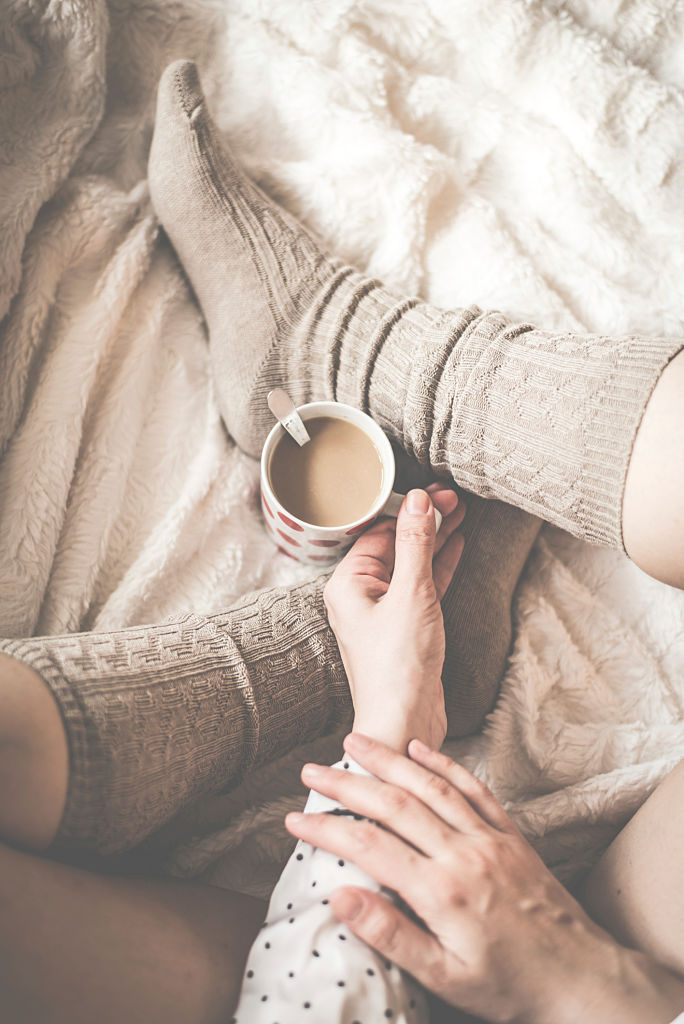 Female legs in knitted socks with cup of coffee