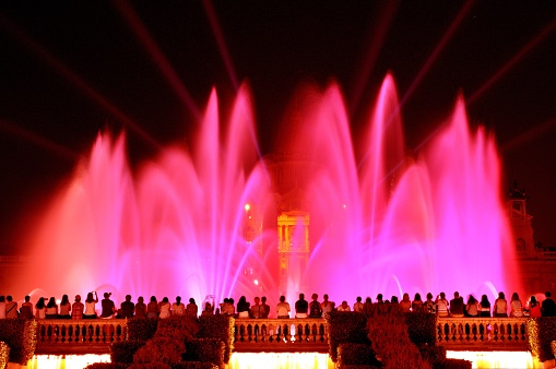 Spain, Catalonia, Barcelona, Spectators watching Fountain of Montjuic located at the head of Avenida Maria Cristina