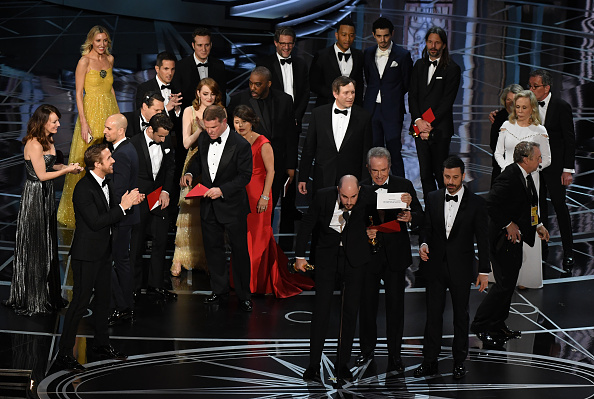 """""""La La Land"""" producer Jordan Horowitz (front C) shows the card saying """"Moonlight"""" won the best picture as actor Warren Beatty (front 4R), and Host Jimmy Kimmel (3R) look on at the 89th Oscars."""